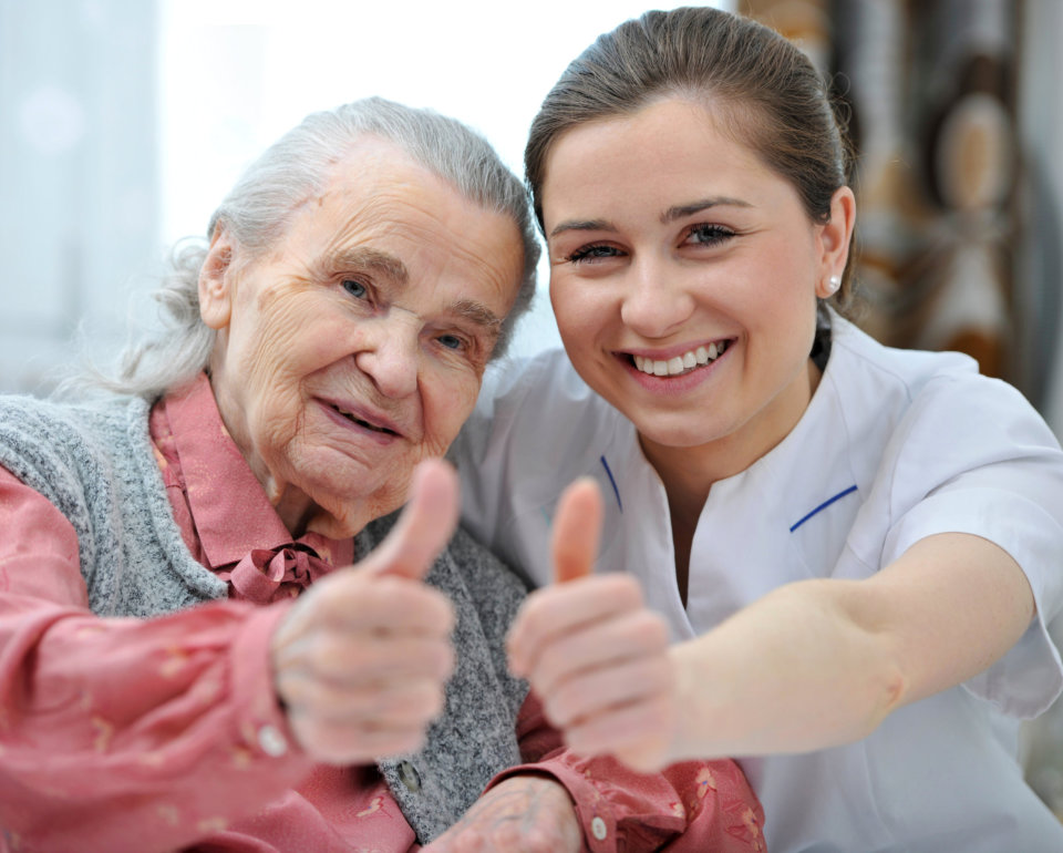 senior woman and caregiver giving thumbs up