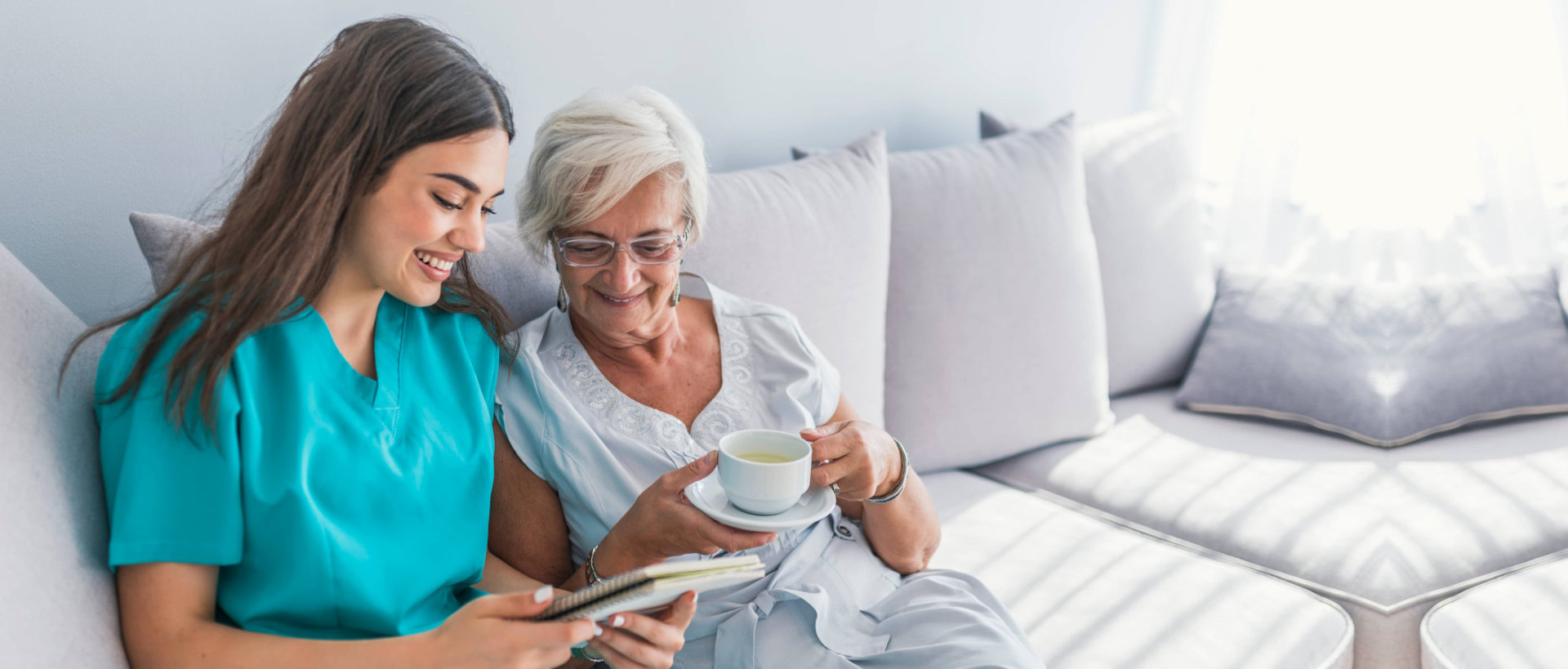 caregiver and senior woman reading a notebook